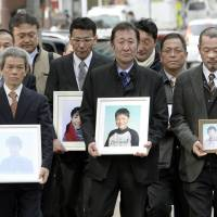 Relatives of Okawa Elementary School students killed in the March 2011 tsunami enter the Sendai District Court on Monday, holding the victims' photos. | KYODO