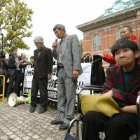 Hideki Sato (center), the leader of an aid group for Minamata disease victims, speaks after the Kumamoto District Court rejected the claims of five of eight unrecognized victims Monday. | KYODO