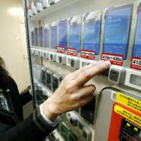 A woman in Minato Ward, Tokyo, points to a sticker on a tobacco vending machine that shows the price of a pack of Mevius cigarettes will be raised from ¥410 to ¥430 on Tuesday, in line with the consumption tax hike.   KYODO