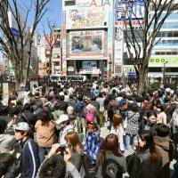 A crowd gathers outside the Studio Alta building in Shinjuku Ward, Tokyo, to watch the final episode of the Fuji TV show 'Waratte Iitomo!' live on a giant screen Monday. | KYODO