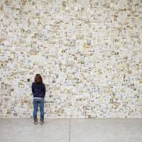 Moving images: A woman contemplates a wall of photos during the exhibition 'From Tsunami, Photographs, and Then: Lost & Found Project.' | SAKURAKO SHIMIZU