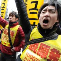 Falling out: Nuclear workers and their supporters shout slogans as they raise their fists in front of the headquarters of Tokyo Electric Power Co., operator of the stricken Fukushima No. 1 nuclear power plant, during a rally in Tokyo on March 14. | AFP-JIJI