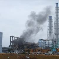 Smoke signal: Wreckage of the Reactor 3 building at Fukushima No. 1 nuclear power plant as seen in a photo released by the operator, Tokyo Electric Power Co., on March 21, 2011. That reactor is now one of three in meltdown at the site. | AP