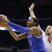 Battle for the Bluegrass: Kentucky's James Young goes up for a shot against Louisville's Stephan Van Treese during the Midwest Regional semifinal. | AP