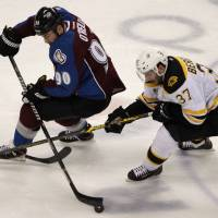 On a roll: The Bruins' Patrice Bergeron (right) competes against Avalanche center Ryan O'Reilly on Friday in Denver. Boston won 2-0. | AP