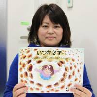 Nana Aihara holds a copy of her book, which describes the pain she has endured since evacuating from Fukushima Prefecture after the March 2011 nuclear disaster.   KYODO