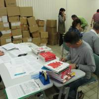 Volunteers sort out books donated by well-known children's book author Taro Gomi in Ota Ward, Tokyo, last April.   KYODO