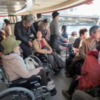 Participants in a field training program to assist the elderly and physically disabled take a ride on a water bus on the Sumida River in Tokyo last November. | KYODO