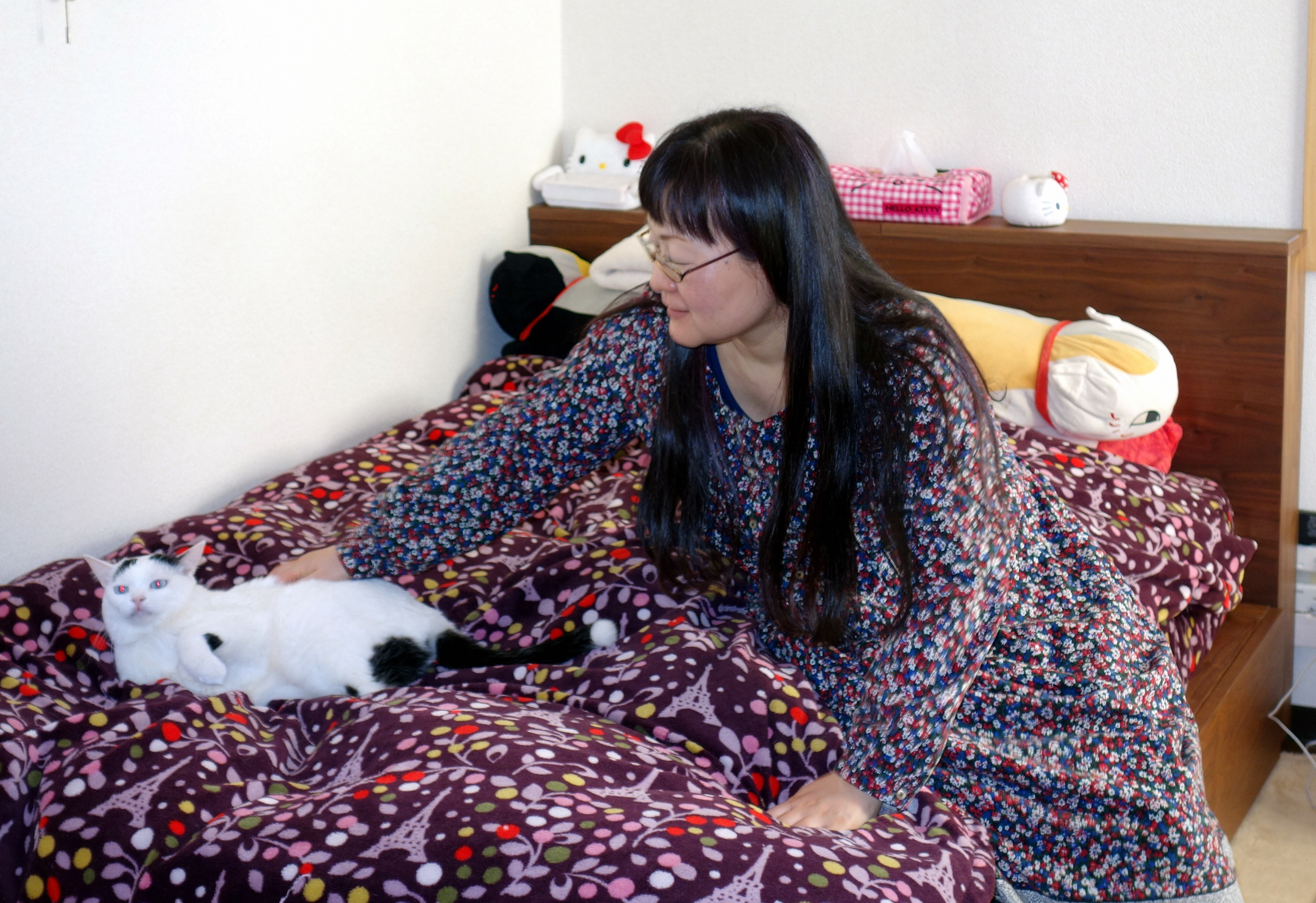Keiko Morishita pets her cat Luna in her Tokyo apartment on March 16. The room was rented under a program in which apartments become 'temporary shelters' for castoff cats. | KYODO