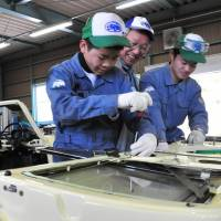 Minoru Ishikawa (center), an adviser to automobile equipment maker Shinmei Industry Co., teaches students how to affix a door to an old Toyota Publica car during a class in Toyota, Aichi Prefecture, in February.   CHUNICHI SHIMBUN