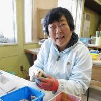 A woman polishes wooden buttons at a community workshop for the disabled in Sukagawa, Fukushima Prefecture, in December.   KYODO