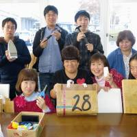 People working at the Futaba Seisakusho workshop in Koriyama, Fukushima Prefecture, make bags using recycled A4-size envelopes decorated with the figure 28. | KYODO