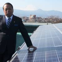 Takeo Minomiya, president of Houtoku Energy Co., poses next to solar panels the firm installed on the roof of an elementary school in Odawara, Kanagawa Prefecture, on Jan. 23. | KYODO