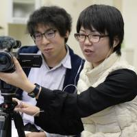Keiko Takahashi (right) and Kai Sato get behind a video camera to practice their interviewing skills on Feb. 8 at Fukushima University ahead of their March visit to the Marshall Islands. | KYODO