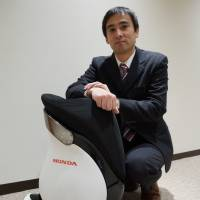 Shinichiro Kobashi, chief engineer at Honda R&D, poses with the Uni-Cub. | KAZUAKI NAGATA