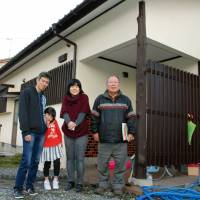Hidetaka Imoto (left) stands with his wife and daughter in front of the house he has rented at Fujimigaoka residential complex in the city of Oita. Standing at right is Yukiyoshi Sasakura, head of a local community association.   KYODO