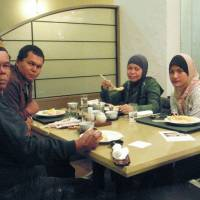 A group of Malaysian tourists enjoy Japanese food prepared in accordance with Islamic laws at Rusutsu Resort Hotel, Hokkaido, in December 2012. Below: This prayer room at Narita International Airport, Chiba Prefecture, is one of several steps aimed at making the airport more amenable to Muslims, who are visiting Japan in greater numbers. | KAMORI KANKO CO./KYODO,TOMOHIRO OSAKI