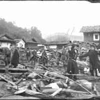 Local residents stand among debris in a photo made from a recently discovered glass-plate negative showing damage from a 1896 earthquake and tsunami in the Sanriku area in northeast Honshu. | MORIOKA LOCAL METEOROLOGICAL OBSERVATORY