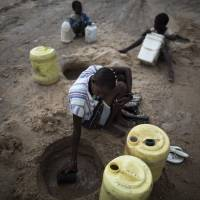 A woman scoops up water from a riverbed in Kenya's drought-stricken Turkana region Thursday after the first downpour in 12 months. A continent plagued by humanitarian crises is increasingly drawing the West's attention for security reasons. | AFP-JIJI