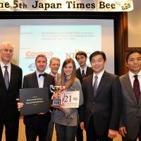 Michaella Bostrom stands with (from left) spelling judge Steve McClure, master of ceremonies Marc Davies, pronouncer James Tschudy, Japan Times Deputy Managing Editor Edan Corkill, Japan Times President Takeharu Tsutsumi and Shigeo Yushita, commercial director and head of Japan for the International New York Times. | YOSHIAKI MIURA