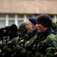 Pro-Russian 'military forces of the autonomous republic of Crimea' attend their swearing-in ceremony at the military enlistment complex in Simferopol, Ukraine, on Monday. | AFP-JIJI