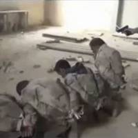 This still image taken from undated footage posted on YouTube shows a member of the Islamic State of Iraq and Levant preparing to execute a row of Iraqi soldiers.   REUTERS