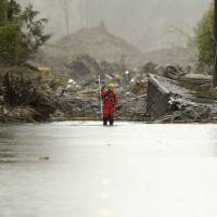 A search worker stands on flooded Highway 530 as efforts continued Thursday in the mud and debris from a massive mudslide that struck Oso, in Washington state, last Saturday. March 27, 2014. | REUTERS