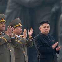 North Korean leader Kim Jong Un (right) claps during an April 2012 unveiling ceremony for statues of his grandfather, Kim Il Sung, and his father, Kim Jong Il, in Pyongyang. | AFP-JIJI