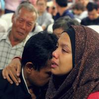 Family members of those onboard Malaysia Airlines Flight MH370 cry at a hotel in Putrajaya, Malaysia, on Sunday. | REUTERS