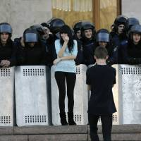 A young man takes photos of his girlfriend in front of a line of Ukrainian riot policemen guarding the regional administration building following a pro-Russian rally in central Donetsk on Sunday. | REUTERS