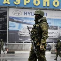 Unidentified armed men patrol Simferopol airport in Ukraine's Crimea region Friday. | AFP-JIJI