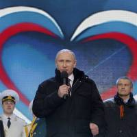 Russian President Vladimir Putin (center) speaks during a rally and concert called 'We are together' to support the annexation of Ukraine's Crimea region by Russia. | REUTERS