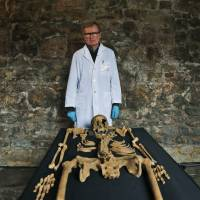 Don Walker, an osteologist with the Museum of London, poses Wednesday with one of the 14th-century skeletons found by construction workers under central London's Charterhouse Square. | AP