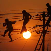 Workers repair electrical wires along the banks of the Ganges in Allahabad, India, one of the world's most energy-thirsty countries, in December 2010. According to a new a U.N. draft report, a little-known process for extracting carbon dioxide may be the radical policy shift needed to slow climate change this century. | AP