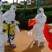 World Health Organization officials prepare to enter Kagadi Hospital in Kibaale, Uganda, where an outbreak of the Ebola virus started in July 2012. On Monday, health officials in Guinea battled to contain West Africa's first outbreak of the deadly virus. | AFP-JIJI