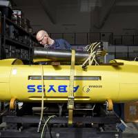 An electrical engineer inspects the Abyss autonomous underwater vehicle at the Helmholtz Center for Ocean Research Kiel in Kiel, Germany, on Monday. The AUV, one of only three unmanned deep-sea search subs in the world, may join the hunt for Malaysia Airlines Flight MH370.   REUTERS