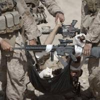 A severely wounded U.S. Marine is carried by his comrades to a medevac helicopter in Afghanistan's Helmand province in October 2011. The U.S. government signed off last week on a long-delayed study looking at marijuana as a treatment for military veterans with post-traumatic stress disorder. | AFP-JIJI