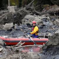 A rescuer uses a small boat to look through debris from a massive mudslide Tuesday in Oso, Washington. At least 16 people were killed in the disaster Saturday. | AP