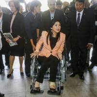 Thai Prime Minister Yingluck Shinawatra arrives in a wheelchair at the Royal Police Cadet Academy in Nakorn Pathom province, west of Bangkok, on Tuesday. | REUTERS
