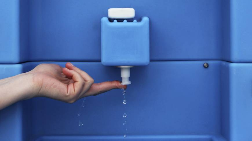 An exhibitor demonstrates a toilet tap that recycles and reuses water during the Reinvent the Toilet Fair in New Delhi.