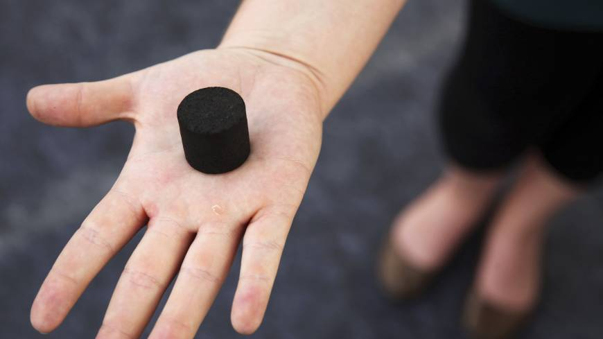 An exhibitor displays biochar, a charcoal-like product made from human waste that can be used as cooking fuel or fertilizer, at the Reinvent the Toilet Fair in New Delhi. | AP