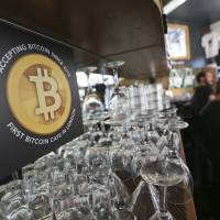 A sign telling customers that the digital currency bitcoin is accepted as payment is displayed behind the counter in the Old Shoreditch Station cafe in London on March 7. | BLOOMBERG