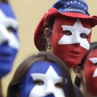 Venezuela opposition supporters wear masks in Droal, Florida, on Friday. | AP
