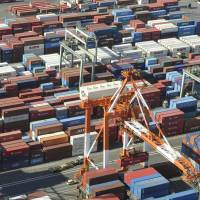 Containers await loading aboard freighters at a Yokohama wharf in January. | KYODO