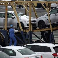 A worker checks a Toyota Motor Corp. vehicle on a transporter ahead of shipment outside the Central Motor Corp. plant in Ohira, Miyagi Prefecture, on Friday. | BLOOMBERG