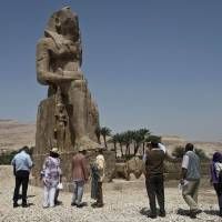 Tourists and journalists stand next to a newly displayed statue of Pharaoh Amenhotep III and his wife, Tiye, in Egypt's temple city of Luxor on Sunday. | AFP-JIJI