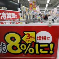 A Bic Camera employee walks by a notice about Tuesday's consumption tax hike to 8 percent from 5 percent at one of the electronics chain's stores in Tokyo Thursday.   BLOOMBERG
