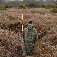 A British Army rifleman holds a pole to measure the height of a WWI practice trench near Gosport, England, on Thursday.   AP