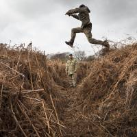 A rifleman leaps across an overgrown trench at a WWI-era practice battlefield in Gosport, southern England, on March 6. | AFP-JIJI