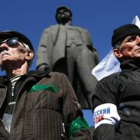 Activists stand guard during a pro-Russian rally in the eastern Ukraine city of Donetsk on Sunday.   AP